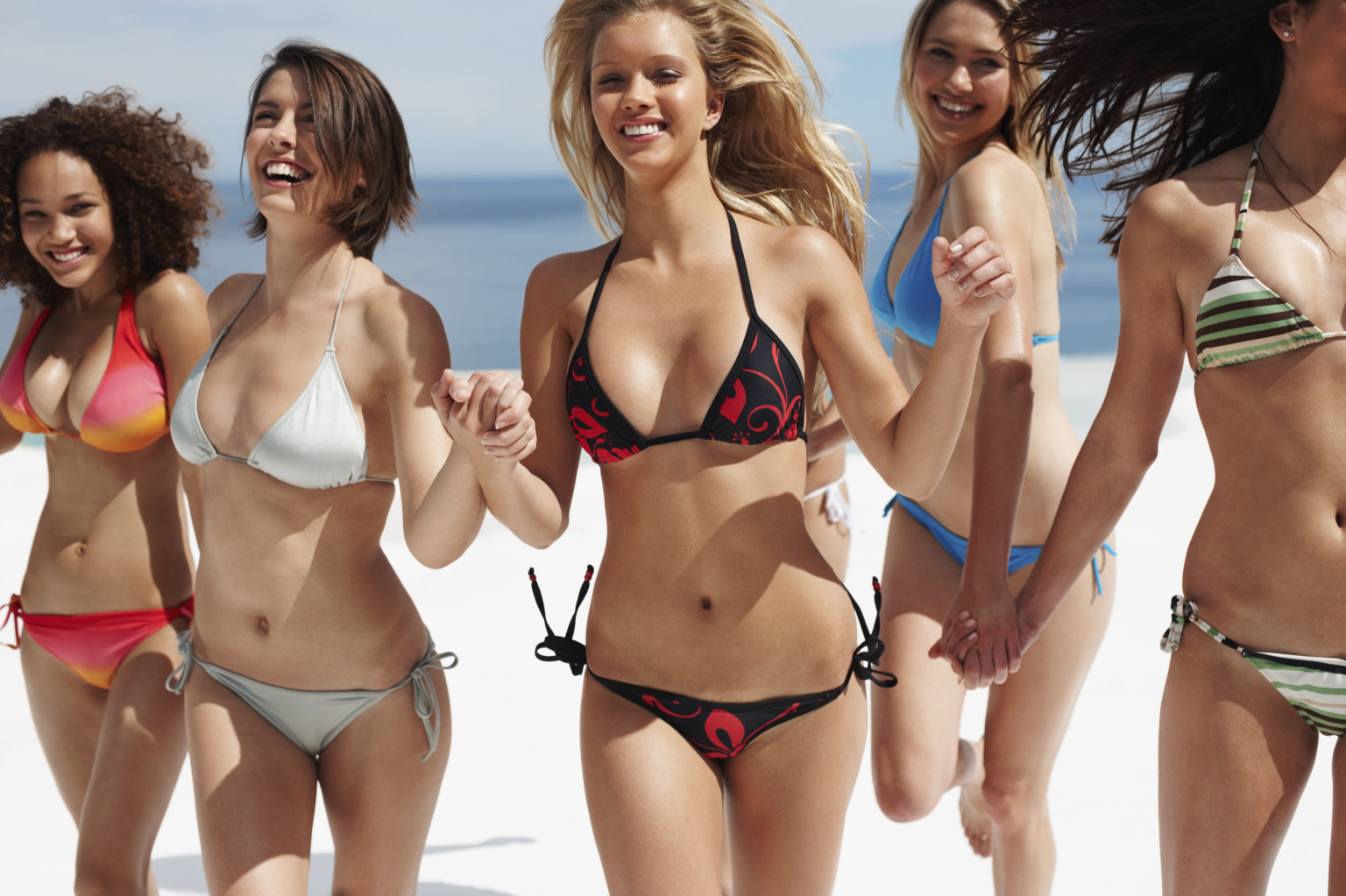 Young group of happy bikini models holding hands and running